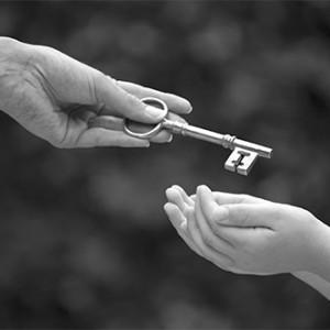Ein Schlüssel wird von einer Person an eine andere weitergegeben.