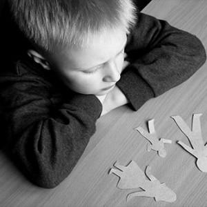 Bild eines Jungen der nachdenklich Papierfiguren die seine Familie darstellen betrachtet