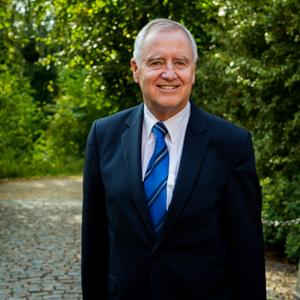 Rechtsanwalt Dr. iur. Gert Maichel steht vor grünem Hintergrund am Winsener Schloss